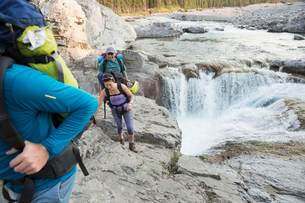 Hikers on rocks above craggy waterfallの写真素材 [FYI02280094]
