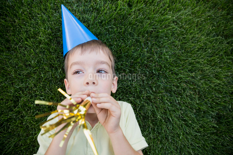Boy in party hat blowing party horn blowerの写真素材 [FYI02280114]