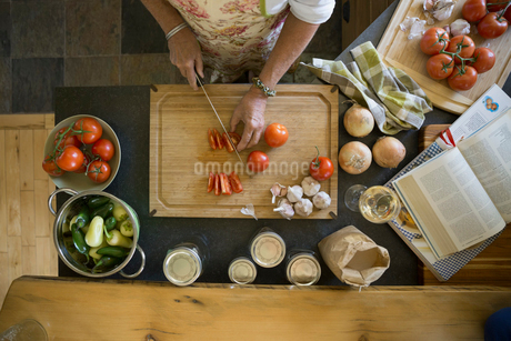 Overhead view woman cutting tomatoes on cutting boardの写真素材 [FYI02280136]