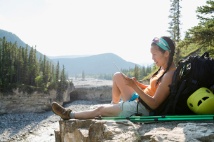 Female backpacker resting with digital tablet on rockの写真素材 [FYI02280190]