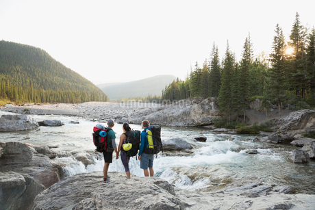 Hikers with backpacks on rock looking river viewの写真素材 [FYI02280206]