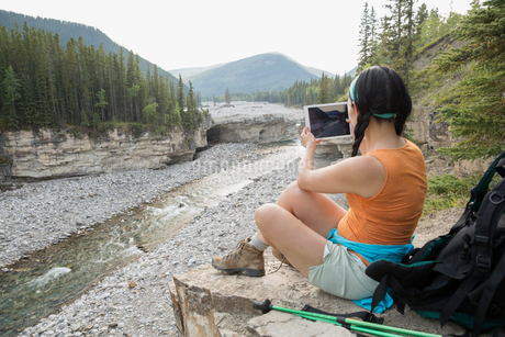 Female backpacker photographing river with digital tabletの写真素材 [FYI02280208]