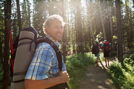 Smiling backpacker on trail in woodsの写真素材 [FYI02280257]