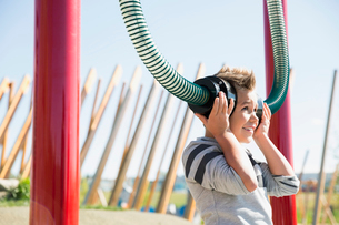 Boy playing listening to tubes in sunny playgroundの写真素材 [FYI02280268]