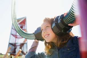 Girl playing listening to tubes in sunny playgroundの写真素材 [FYI02280276]