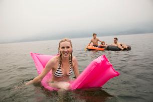 Portrait smiling woman on pool raft in lakeの写真素材 [FYI02280295]