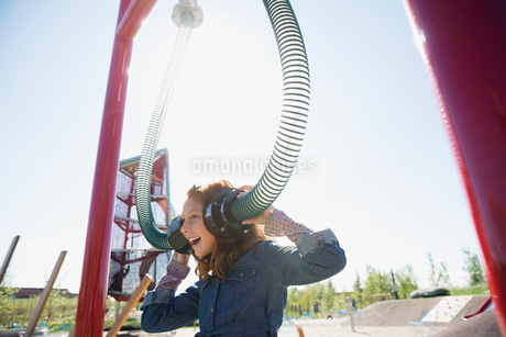 Girl playing listening to tubes in sunny playgroundの写真素材 [FYI02280333]