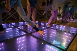 Barefoot girls dancing illuminated floor science center exhibitの写真素材 [FYI02280466]