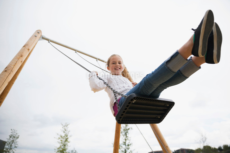 Portrait smiling girl swinging at playgroundの写真素材 [FYI02280536]