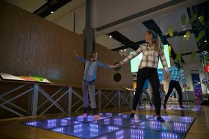 Mother daughter dancing illuminated floor science center exhibitの写真素材 [FYI02280548]