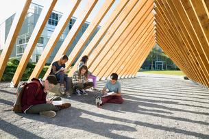 Students doing homework under wood beam walkwayの写真素材 [FYI02280751]