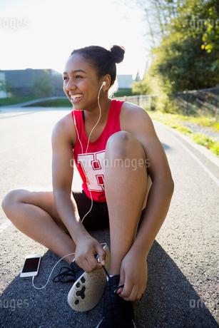 Smiling high school athlete tying shoe listening musicの写真素材 [FYI02280770]