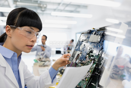 Engineer with paperwork examining circuit boardの写真素材 [FYI02280791]