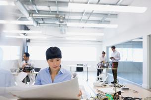 Engineer reviewing blueprints in robotics factoryの写真素材 [FYI02280804]