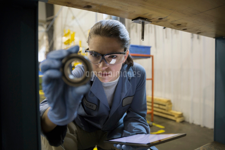 Focused worker with digital tablet examining part factoryの写真素材 [FYI02280835]