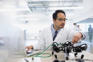 Engineer at laptop assembling robotics at deskの写真素材 [FYI02280838]