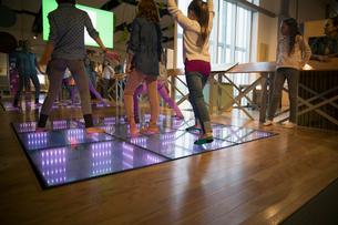 Girls dancing on illuminated floor at science centerの写真素材 [FYI02280916]