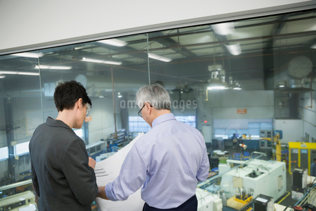 Managers reviewing blueprints at factory windowの写真素材 [FYI02280940]