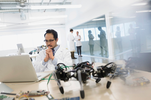 Focused engineer working at laptop near roboticsの写真素材 [FYI02280941]