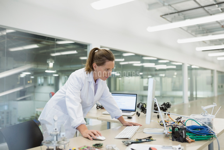 Engineer working at computer with robotics in factoryの写真素材 [FYI02280993]