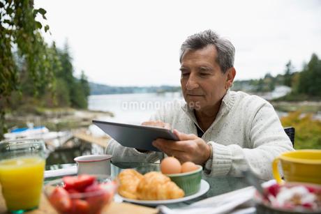 Senior man with digital tablet enjoying breakfast lakesideの写真素材 [FYI02280999]