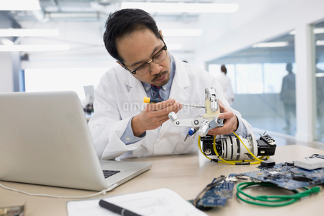 Engineer at laptop assembling robotics at deskの写真素材 [FYI02281003]