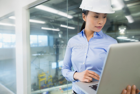 Engineer with laptop in factoryの写真素材 [FYI02281013]