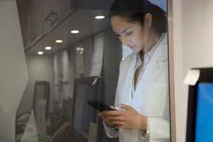 Doctor texting at glass wall in clinicの写真素材 [FYI02281031]
