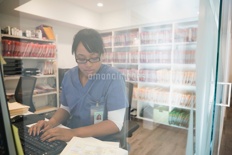 Nurse typing medical record notes at computerの写真素材 [FYI02281042]