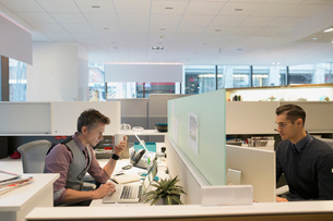 Businessmen working in cubicles in officeの写真素材 [FYI02281067]
