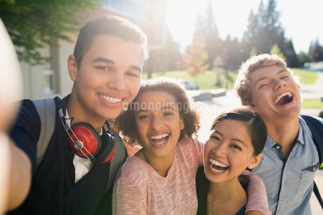 Portrait playful high school students taking selfie outdoorsの写真素材 [FYI02281153]