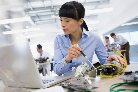 Engineer at laptop assembling robotics at deskの写真素材 [FYI02281165]