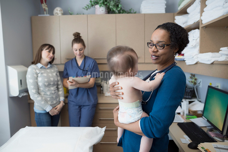 Pediatrician holding baby in examination roomの写真素材 [FYI02281168]