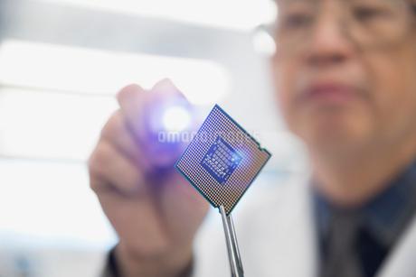 Focused engineer examining microchip with flashlightの写真素材 [FYI02281292]