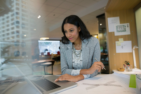 Young female architect using laptop at office deskの写真素材 [FYI02281401]