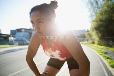 Serious high school athlete hands knees running trackの写真素材 [FYI02281442]