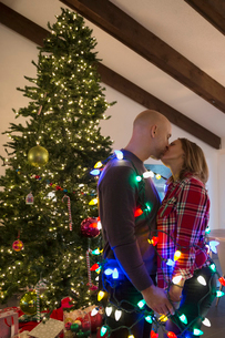 Couple wrapped in Christmas string lights kissingの写真素材 [FYI02281466]