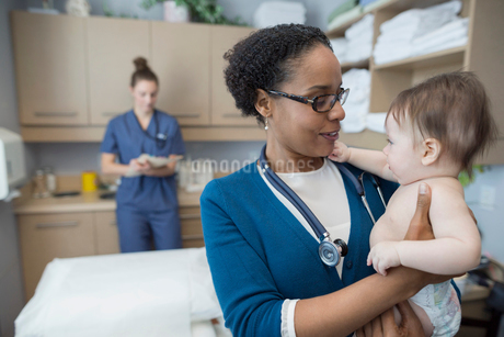 Pediatrician holding baby in examination roomの写真素材 [FYI02281534]