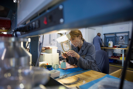 Worker examining part with magnification glass in factoryの写真素材 [FYI02281573]
