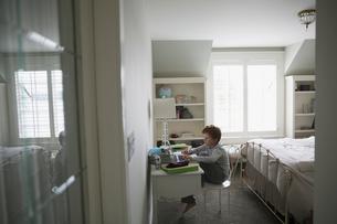 Boy doing homework at desk in bedroomの写真素材 [FYI02281648]