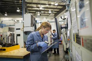 Worker scanning paperwork on clipboard in factoryの写真素材 [FYI02281688]
