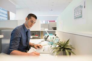 Focused businessman using laptop at office deskの写真素材 [FYI02281841]