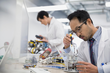 Engineers assembling robotics in factoryの写真素材 [FYI02281842]