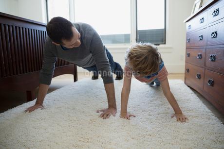 Father teaching son push-ups on bedroom rugの写真素材 [FYI02281887]