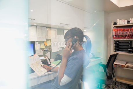 Nurse talking on telephone at nurses stationの写真素材 [FYI02281925]
