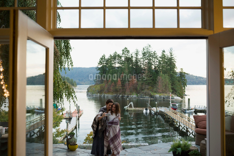 Mother and daughter wrapped blankets selfie lakeside patioの写真素材 [FYI02282007]