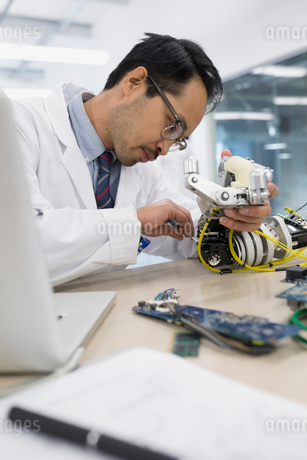 Engineer at laptop assembling robotics at deskの写真素材 [FYI02282024]