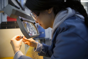 Worker using magnification glass to examine part factoryの写真素材 [FYI02282054]