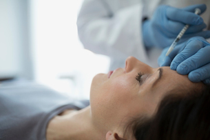 Woman receiving Botox injection in foreheadの写真素材 [FYI02282104]