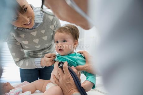 Pediatrician examining baby with stethoscope in examination roomの写真素材 [FYI02282166]